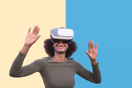 Afro woman using virtual reality glasses outdoor - Happy young girl having fun with innovated vr  technology - Tech lifestyle entertainment and 3d game experience concept