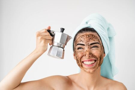Young smiling woman applying coffee scrub mask on face - Happy girl having healthy skin care spa day at home - Alternative natural exfoliation treatment and people lifestyle concept