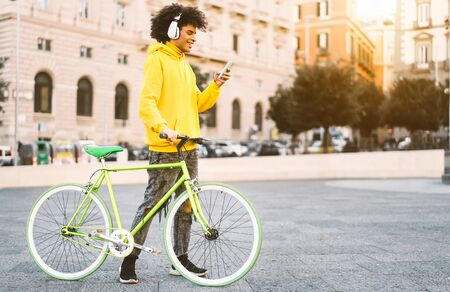 Happy Afro man using mobile smartphone outdoor - Young guy having fun listening music with headphones while riding with bike in city - Youth millennial generation lifestyle and technology concept