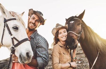Happy couple having fun with horses inside stable - Young farmers sharing time with animals in corral ranch - Human and animals relationship lifestyle concept