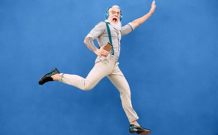 Senior crazy man jumping while listening music with wireless headphones - Hipster old guy having fun dancing outdoor - People happiness and elderly technology addicted concept - Blue background Banque d'images