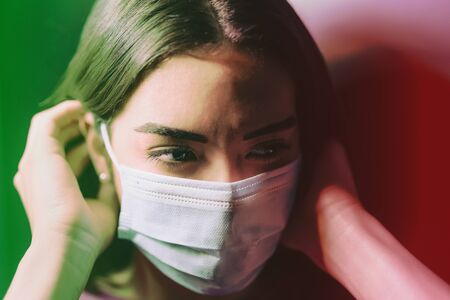 Young woman wearing face surgical mask against corona virus - Fear girl quarantine for preventing pandemic spread of coronavirus - Mental health impact during covid-19 and anxiety people concept 版權商用圖片