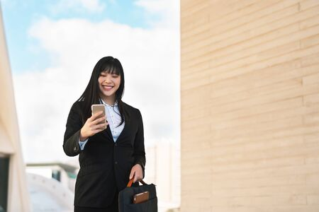 Business Asian woman using mobile smartphone out office - Young smiling Chinese girl ready for working - Apprenticeship and entrepreneurship job concept 版權商用圖片
