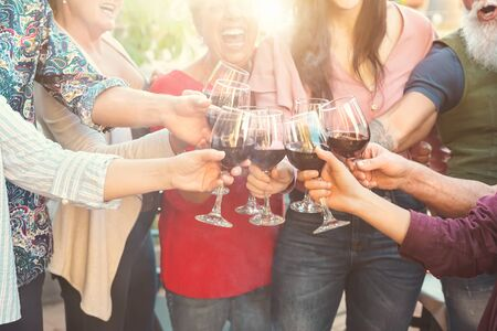 Happy family toasting with red wine glasses at dinner outdoor - People having fun cheering and drinking while dining together - Food and beverage weekend lifestyle activities Stok Fotoğraf
