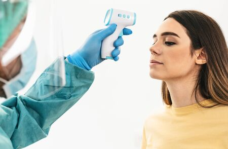 Doctor measuring temperature with new digital thermometer to young woman patient during corona virus pandemic - Health care and medical equipment concept