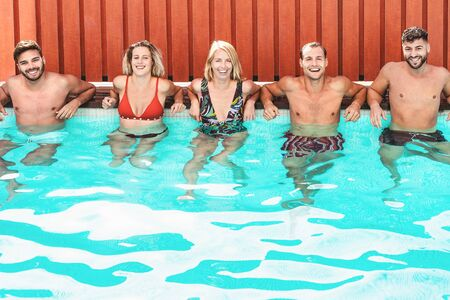 Happy friends enjoying summer day in swimming pool - Young people having fun in exclusive private villa - Youth vacation lifestyle concept