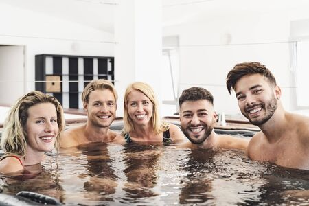Happy friends enjoying vacations in bath tub luxury house - Young people having fun together in hot tub - Youth millennial generation and wellness lifestyle holidays Reklamní fotografie