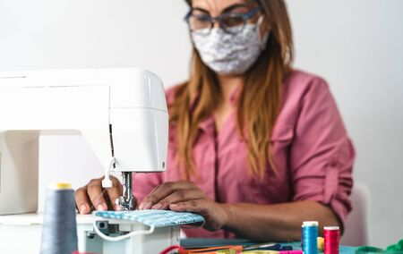 Mature woman working with sewing machine doing homemade medical face mask for preventing and stop corona virus spreading - Textile seamstress and healthcare people concept