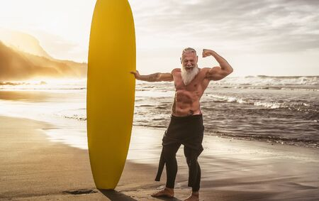 Happy fit senior having fun surfing at sunset time - Sporty bearded man training with surfboard on the beach - Elderly healthy people lifestyle and extreme sport concept