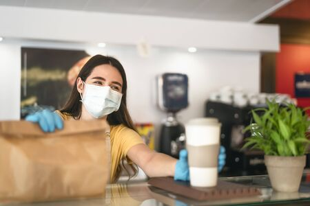 Bar owner working only with take away orders during corona virus outbreak - Young woman worker wearing face surgical mask giving meal to customers - Healthcare and Food drink concept