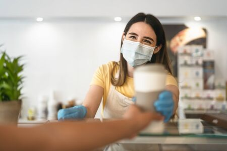 Bar owner working only with take away orders during corona virus outbreak - Young woman worker wearing face surgical mask giving coffee to customer - Healthcare and drinks concept Reklamní fotografie