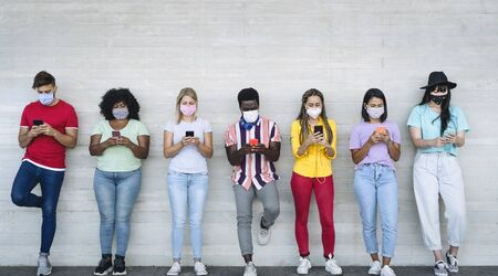 Young people wearing face mask using mobile smartphone outdoor - Multiracial friends having fun with new technology social media app during corona virus outbreak - Youth millennial lifestyle concept Stockfoto