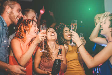 Happy friends doing party drinking champagne in nightclub - Group young people having fun celebrating new year eve holidays together in disco club - Youth culture entertainment lifestyle concept Reklamní fotografie