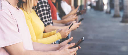 Group friends using mobile smartphones outdoor - Millennial young people addicted to new technology trends apps - Youth social generation lifestyle concept