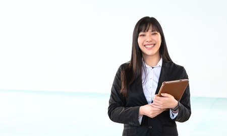 Asian business woman holding smart mobile tablet in office - Young smiling Chinese girl ready for working on digital marketing - Technology apprenticeship and entrepreneurship professional job concept Reklamní fotografie