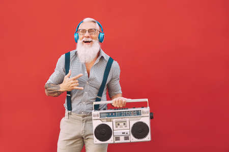 Senior crazy man listening music with headphones and vintage boombox outdoor - Hipster male having fun living in past time - Elderly people lifestyle activity - Red background Banque d'images
