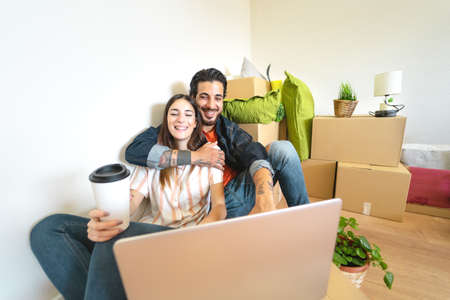 Happy young couple moving in new home first time - Man and woman having fun using computer next carton box in new property house - Change apartment day and people lifestyle relationship concept Reklamní fotografie