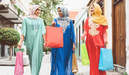 Happy Muslim women doing shopping in the city center - Arabian teen girls having fun buying new traditional Arab clothes in mall - Concept of people religion, shopper, consumerism and diverse culture
