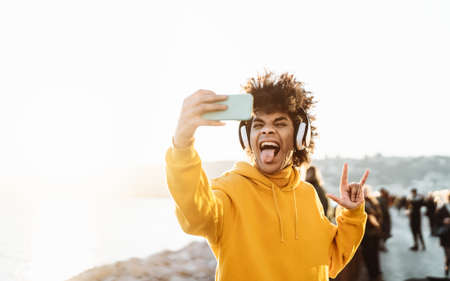 Young Afro man taking self video while listening music with wireless headphones - Happy mixed race guy having fun with new technology apps for mobile smartphone - Millennial lifestyle concept