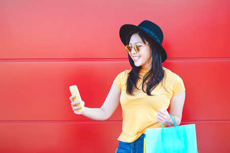 Asian fashion girl doing shopping in mall center using mobile smartphone - Happy Chinese woman having fun buying new clothes in vacation - Consumerism, people and youth lifestyle concept