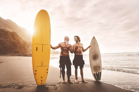 Happy friends surfing together on tropical ocean - Sporty people having fun during vacation surf day - Elderly and youth extreme sport lifestyle concept