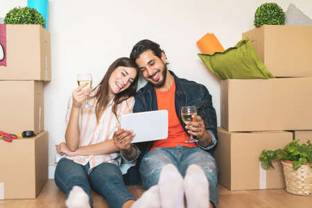 Happy young couple moving in new property house - Young lovers having fun using tablet shopping online sitting next carton box - Change apartment day and people lifestyle relationship concept