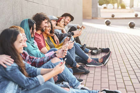 Group trendy friends using smart mobile phones outdoor - Millennial people having fun with new technology trends smartphone - Youth generation lifestyle and tech addiction social media concept