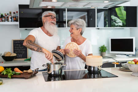 Happy senior couple having fun cooking together at home - Elderly people preparing health lunch in modern kitchen - Retired lifestyle family time and food nutrition concept Reklamní fotografie
