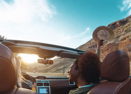 Young women doing road trip in tropical city - Travel happy people having fun driving in trendy convertible car discovering new places - Friendship and youth girlfriends vacation lifestyle concept