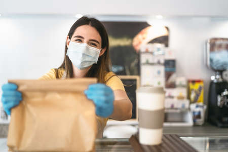 Bar owner working only with take away orders during corona virus outbreak - Young woman worker wearing face surgical mask giving takeout meal to customers - Healthcare and Food drink concept Reklamní fotografie