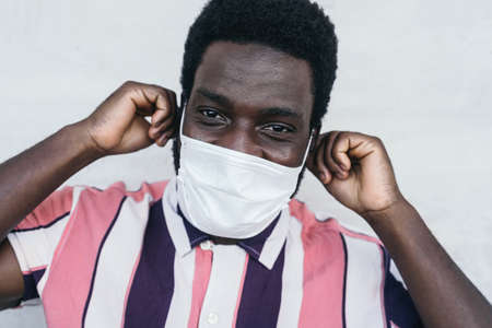 Young African man wearing face mask portrait - Afro American boy using protective facemask for preventing spread of corona virus - Health care and pandemic crisis concept