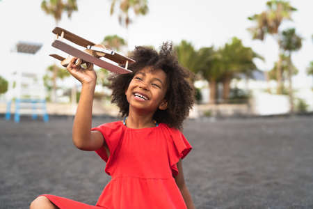 Afro child playing with wood toy airplane on the beach - Little kid having fun during summer holidays - Childhood and travel vacation concept Reklamní fotografie