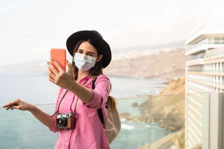 Young travel woman taking selfie with mobile smartphone wearing face surgical mask - Travel influencer having fun in vacation during corona virus outbreak - Millennial people and technology concept