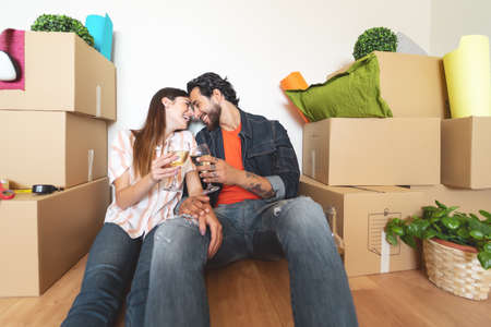 Happy young couple moving in new home first time - Man and woman having celebrating with champagne in new property house - Change apartment day and people lifestyle relationship concept