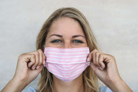 Young woman wearing pink face mask portrait - Blonde female using protective facemask for preventing spread of corona virus - Health care and pandemic crisis concept