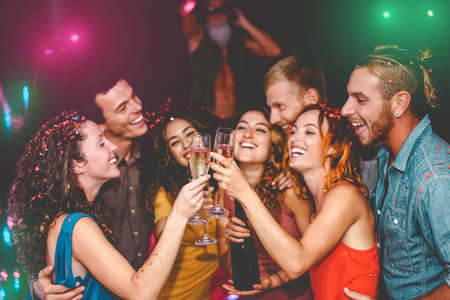 Happy friends celebrating new year eve holidays in disco club - Young people doing private party with deejay and drinking champagne - Youth culture entertainment lifestyle concept Reklamní fotografie