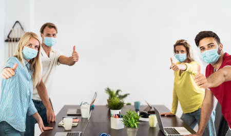 Young people working in co-working creative space wearing surgical mask protection for preventing corona virus spread - Social distancing, content creator startups and technology concept Stock fotó