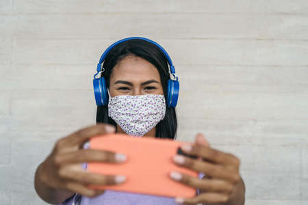 Young Latin woman taking selfie and listening music with wireless headphones while wearing face mask - Happy girl having fun with mobile smartphone during corona virus outbreak