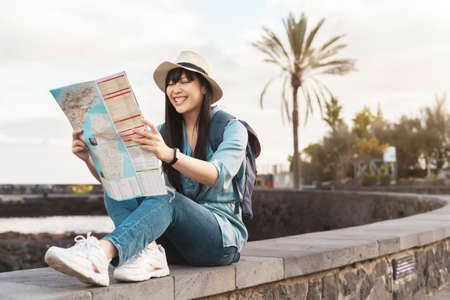 Travel Asian girl looking map during city tour - Young happy woman doing old town excursion discovering new places - Vacation people and sightseeing historic city concept