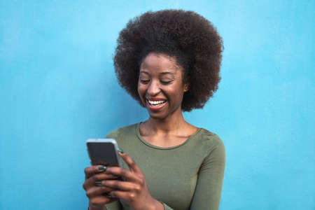 Young Afro woman using mobile smartphone - Happy African girl having fun with new trends technology apps - Youth millennial generation z and social influencer concept - Blue background Stock fotó