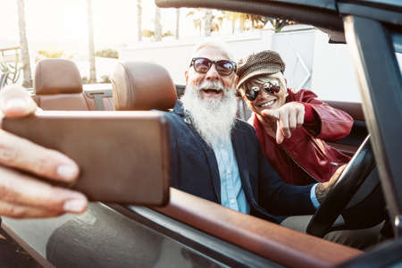 Happy senior couple taking selfie on new convertible car - Mature people having fun in cabriolet together during road trip vacation - Elderly lifestyle and travel transportation concept