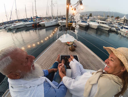 Senior couple on sailboat vacation - Happy elderly people having fun celebrating wedding anniversary on boat trip - Love relationship and travel lifestyle concept
