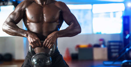 Young African man training exercises inside gym - Fit male doing kettlebell workout session in sport club center - Fitness and bodybuilding lifestyle concept