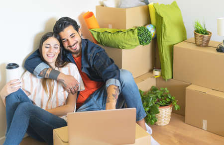 Happy young couple moving in new home first time - Man and woman having fun using computer next carton box in new property house - Change apartment day and people lifestyle relationship concept Stock fotó