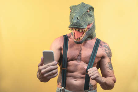 Senior man taking selfie with smartphone while wearing dinosaur mask - Mature social influencer having fun with mobile app - People lifestyle and technology concept