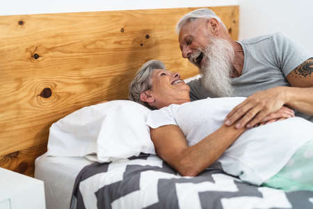 Happy senior couple in bed - Hipster mature people having funny bed time together - Elderly lifestyle and love relationship concept