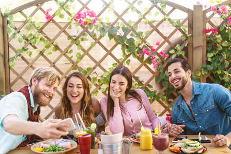 Happy friends taking selfie with mobile smartphone while lunching in coffee brunch restaurant - Young trendy people having fun eating together - Youth tech lifestyle food culture concept