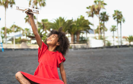 Afro child playing with wood toy airplane on the beach - Little kid having fun during summer holidays - Childhood and travel vacation concept Stock fotó