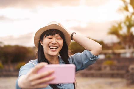 Happy Asian girl taking selfie with mobile smartphone during vacation - Travel Chinese woman having fun with new trends technology apps - Millennial generation and tech social people addicted concept