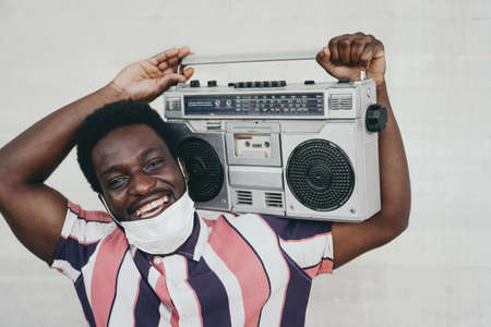Young African man holding vintage boombox having fun outdoor - Black man wearing face mask while listening music with stereo during corona virus pandemic - Youth people and covid19 outbreak concept Stock fotó